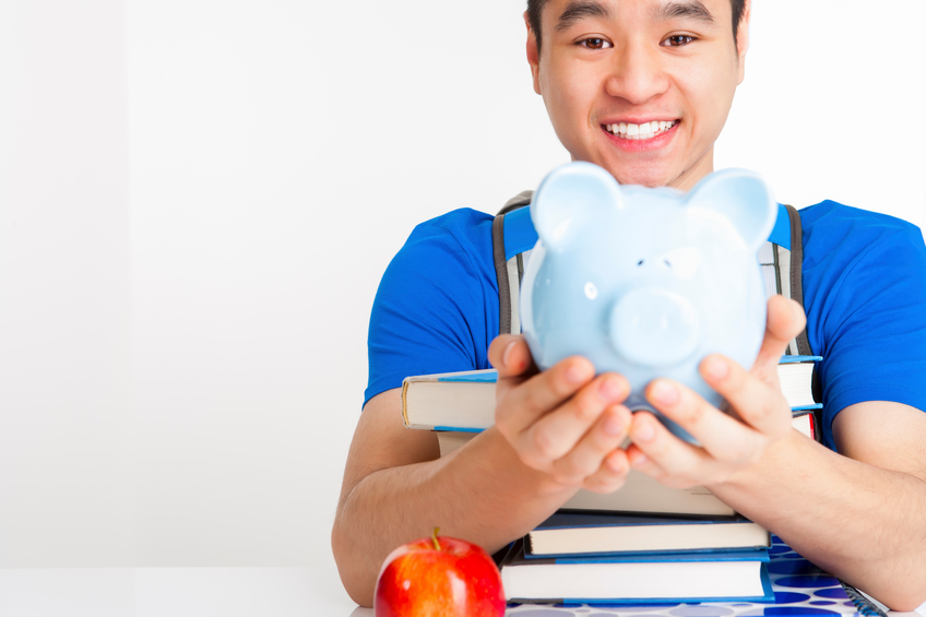 Smiling male student holding piggy bank